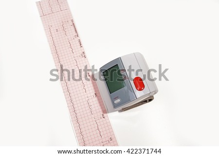 Electrocardiogram Result.Electrocardiogram ecg heart beat test in paper and blood pressure monitor isolated on the white background. - stock photo