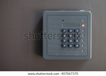 electronic access control door box with numeric keypad on dark gray background  - stock photo