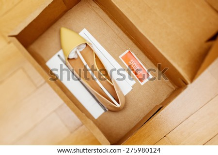 Electronic article surveillance or security tag placed in a shoe box to prevent shoplifting (also known as boosting and five-finger discount)  - stock photo