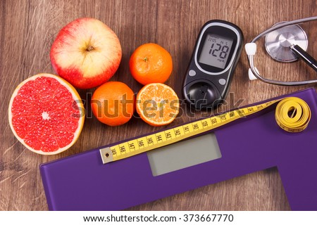 Electronic bathroom scale and glucose meter with result of measurement sugar level, healthy food and stethoscope, concept of healthy lifestyles, diabetes and slimming - stock photo