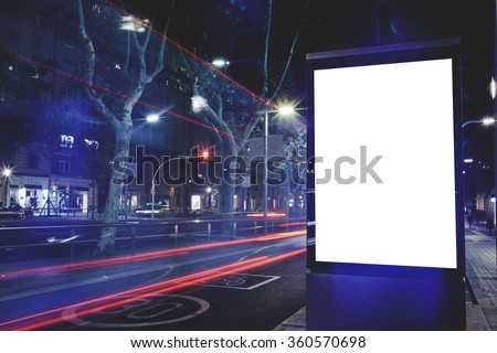 Electronic blank billboard with copy space for your text message or content, public information board with cars lights on background, advertising mock up in urban setting, empty poster on roadside - stock photo