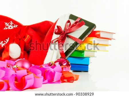 Electronic book reader with stack of books in bag against white background - stock photo
