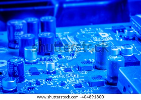 Electronic capacitors and chips on a microboard in blue color - stock photo