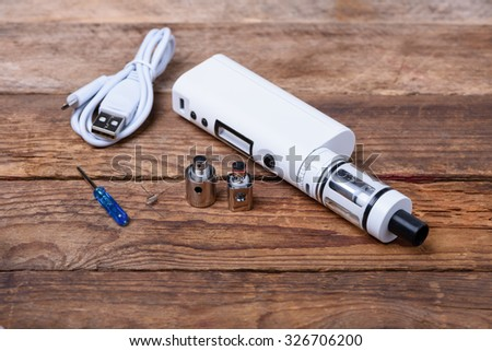 Electronic cigarette with coils, atomizer and heads on wooden table still life - stock photo