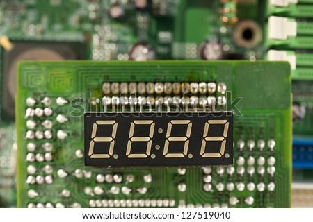 electronic circuit board  and digital clock show zero hours zero minutes - stock photo