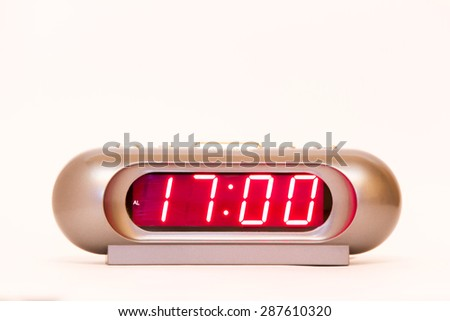 electronic clock alarm clock with red illumination and the time 17:00 - stock photo