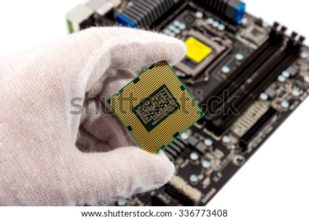 Electronic collection - The repairman holding computer processor in hand before installation into the motherboard - stock photo