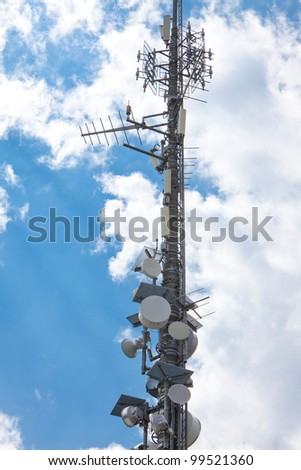 Electronic communications and cell phone tower under partially cloudy sky. Vertical format.