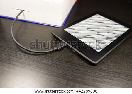 Electronic device for reading books (ereader, ebook), concept of downloading a book on the device. selective focus - stock photo