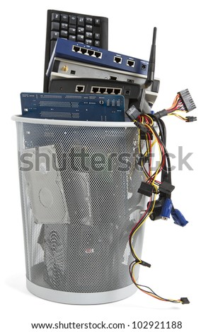 electronic scrap in trash can. keyboard, power supply, router, cables, logicboard, hard drive, switch - stock photo