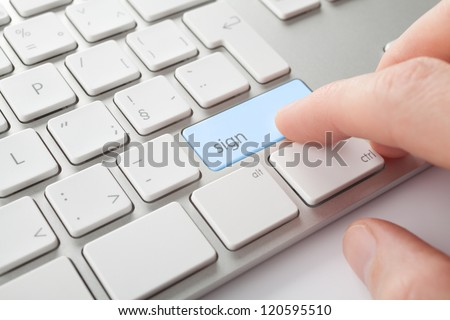Electronic signature concept. Man press sign key on computer keyboard.