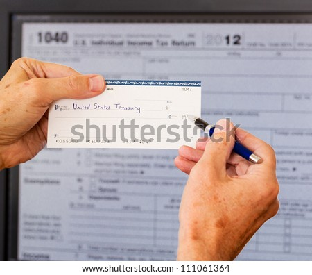 Electronic tax form 1040 for 2012 for US individual return on screen with check payable to US Treasury - stock photo