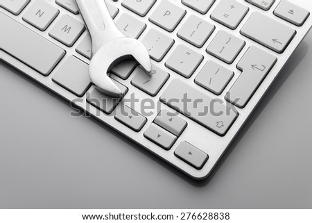 electronic technical support concept - spanners on computer keyboard - stock photo