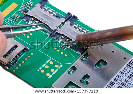 Electronic technician operates with SIM slot on mobile phone circuit board. Close-up with selective focus and Shallow Depth of Field. Isolated on white background. - stock photo