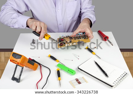 Electronic test engineer using long nose pliers mount component in a circuit board on his white topped work bench - stock photo