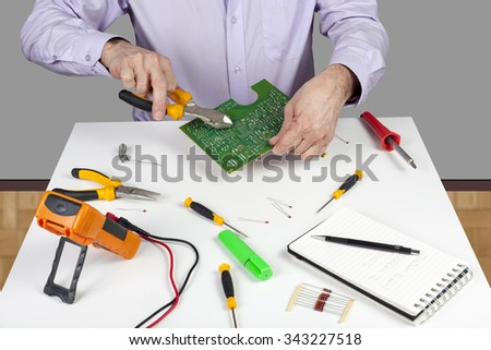 Electronic test engineer using side cutters to trim a soldered component on PCB on his white topped work bench - stock photo