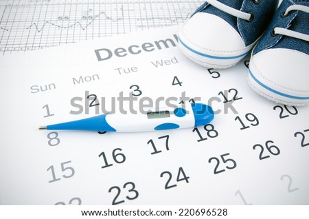 Electronic thermometer in fertility concept on calendar - stock photo