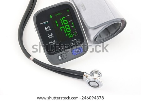 Electronic upper arm blood pressure monitor and stethoscope on white background. - stock photo