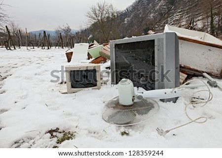 electronic waste and electrical appliance abandoned in the snow -  illegal waste dump in the countryside - stock photo