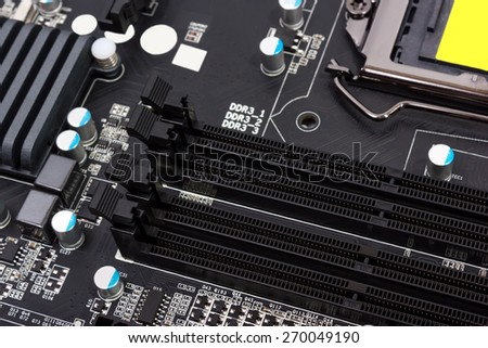 Electronics components on modern PC computer motherboard with RAM connector slot - stock photo