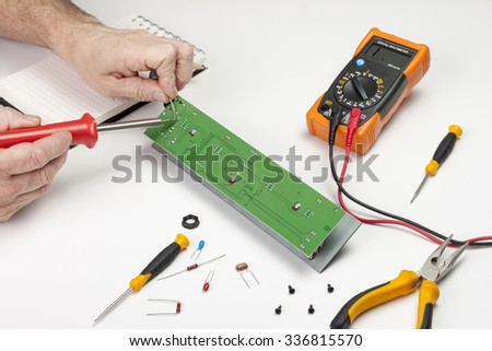 Electronics engineer soldering component to a circuit board - stock photo