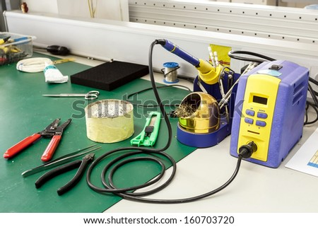 electronics equipment assembly workplace with solder and necessary tools - stock photo