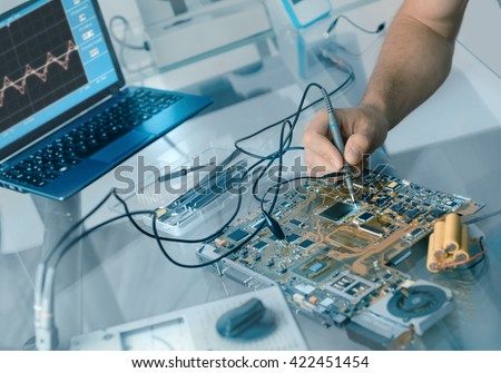 Electronics repair background. Hand of male tech testing motherboard. Shallow DOF, focus on the hand and part of the motherboard. This image is toned.