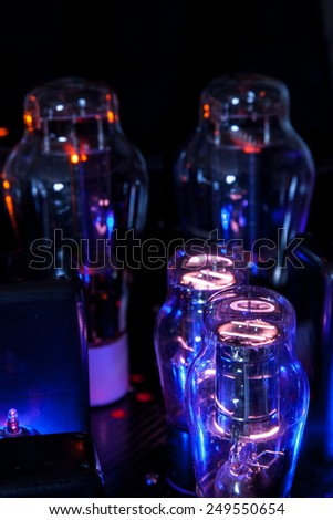 Electronics Vacuum tubes of a hi fi amplifier in a dark room: incandesent filament and ionized gas - stock photo