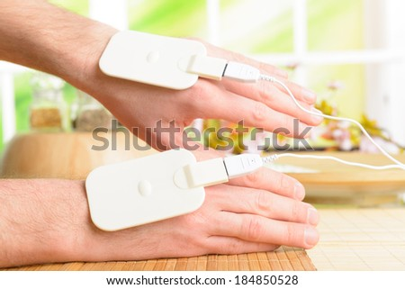 Electrotherapy, electrical stimulation using surface electrode pads with a conductor gel placed on the skin.  - stock photo
