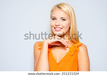 Elegance and beauty. Beautiful young blond hair woman in pretty dress holding hand on chin and smiling while standing against grey background   - stock photo