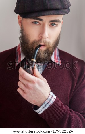 Elegance and masculinity. Portrait of handsome young man in hat smoking a pipe and smiling at camera