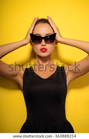 Elegance and style. Studio portrait of gorgeous young woman in little black dress posing against yellow background. - stock photo