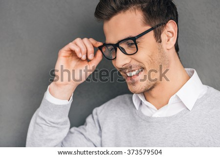 Elegance and success. Side view of confident young man adjusting his glasses and looking away with smile while standing against grey background - stock photo