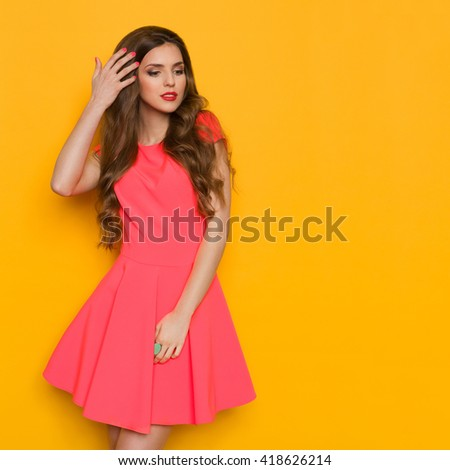 Elegance beautiful young woman in pink mini dress  holding her long brown curly hair and looking away. Three quarter length studio shot on yellow background. - stock photo