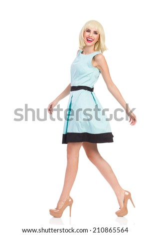 Elegance blond young woman walking and smiling at camera. Side view. Full length studio shot isolated on white. - stock photo