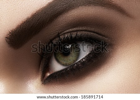 Elegance close-up of female eye with classic dark brown smoky make-up. Macro shot of woman's face part. Beauty, cosmetics and makeup.  - stock photo