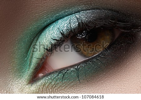 Elegance close-up of female eye with mint color eyeshadow. Macro shot of face part - stock photo