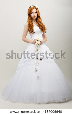 Elegance. Cute Redhaired Bride with Bouquet of Flowers in white Bridal dress - stock photo