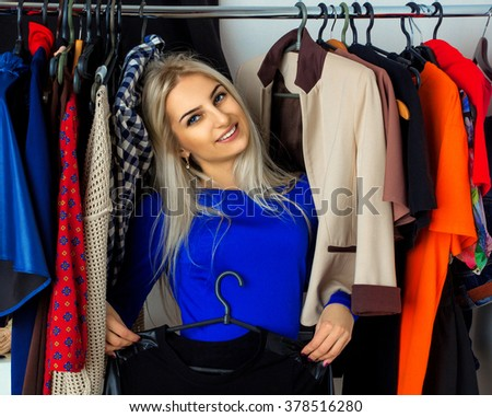 Elegance young blonde woman in clothing store smiling on camera. Happy young lady with a lot of clothes. Shopping concept.
