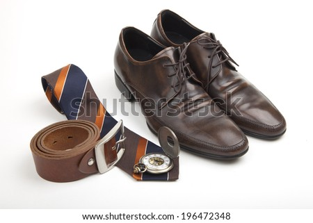 Elegant accessories for the businessman with a brown leather belt, striped brown, blue and gold tie, pocket watch and classic brown lace-up shoes arranged on white - stock photo
