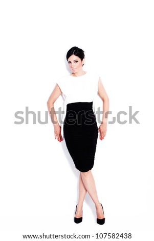 elegant adult woman in black and white dress full body shot studio white - stock photo
