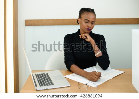 Elegant African or black American woman holding chin with hand writing in notepad - stock photo