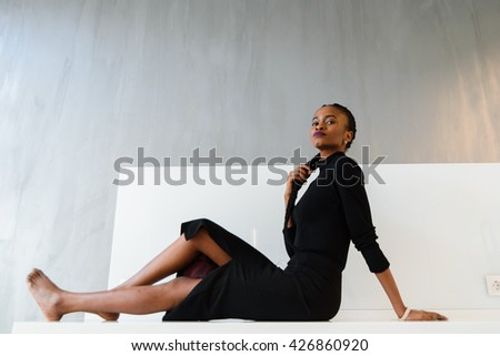 Elegant african or black american woman in dark dress posing on desk in light interior