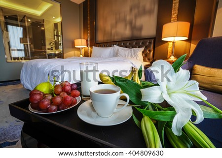 Elegant and comfortable home & hotel bedroom interior as background, A glass of milk,cup of tea,bananas and grapes with lily flowers at bed. - stock photo
