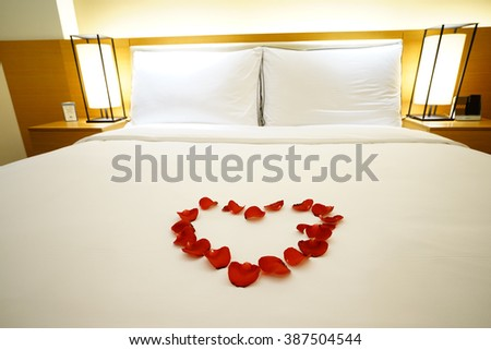 Elegant and comfortable home & hotel bedroom interior as background, the Rose Petals at bed, romantic style. - stock photo