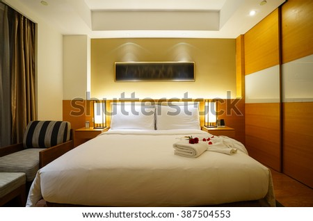 Elegant and comfortable home & hotel bedroom interior.the red carnation flowers and bath towel at bed.