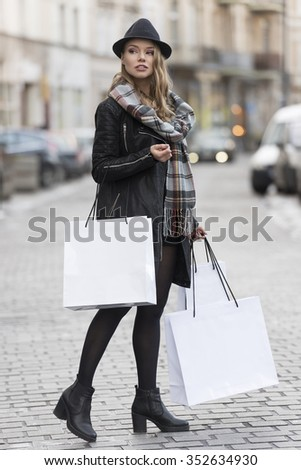 elegant and cute woman , in the middle of a road , with shopping bag for winter sale , she is wearing scarf and a nice hat