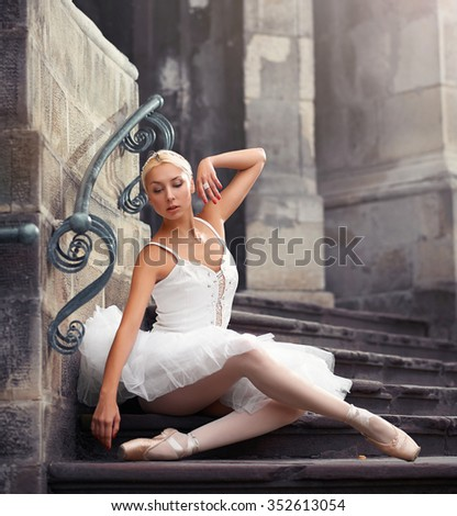 Elegant and feminine. Portrait of an attractive ballerina posing sensually on the stairs of an old castle  - stock photo