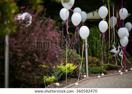 Elegant and fun decorated path to wedding aisle with white balloons and colorful ribbons - stock photo