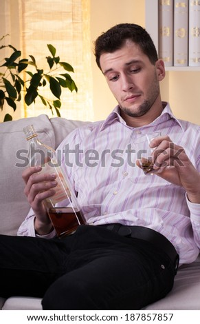 Elegant and handsome man drinking alcohol at home